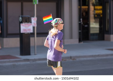 Boulder, Colorado / United States of America - September 8th, 2019 : A person runs in the Rainbow Run Walk 5k, with a small rainbow flag in the back of their bandana during Boulder Pridefest.