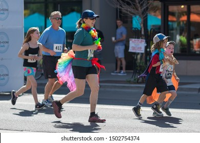 Boulder, Colorado / United States of America - September 8th, 2019 : A family in bright colors and costumes runs together during the Rainbow Run Walk 5k at Boulder Pridefest.