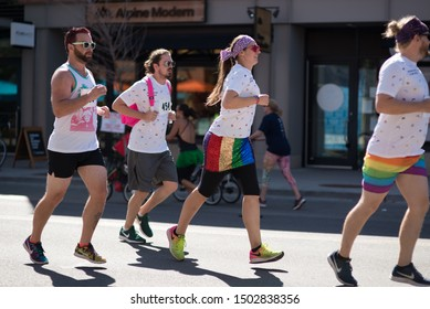 Boulder, Colorado / United States of America - September 8th, 2019 : A group of people participating in the Rainbow Run Walk 5k, wearing rainbow clothes and flags during Boulder Pridefest.