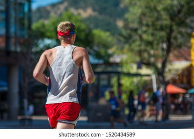 Boulder, Colorado / United States of America - September 8th, 2019 :  A male runner heads through downtown wearing a rainbow headband on a sunny morning during the Rainbow Run Walk 5k at Pridefest.