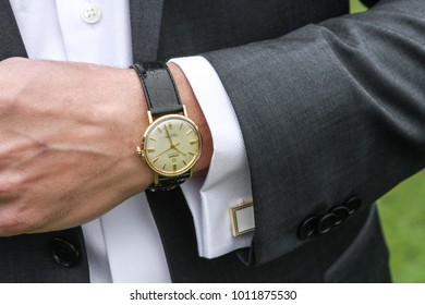 Boulder, Colorado / United States - May 10, 2015: Men's analog wrist watch and charcoal men's suit with white dress shirt and white cuff links
