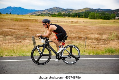 Boulder, Colorado, USA - July 24, 2016: A triathlete bikes along Nelson Road during Tri Boulder.