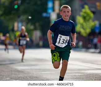 Boulder, Colorado, USA - July 28, 2016: Charlton McDermitt focuses intently as he nears the finish of the West End 1K kids race along Pearl Street in downtown Boulder.