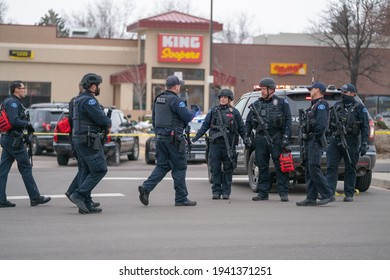 Boulder, Colorado USA - March 22, 2021: Police officers standing around cars and in front of King Soopers - the scene of a mass shooting
