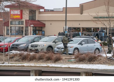 Boulder, Colorado USA - March 22, 2021: A police officer in tactical gear walking around cars in front of King Soopers - the scene of a mass shooting