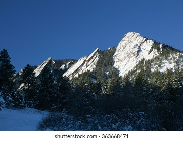 The Boulder Flatirons freshly dusted with snow on a sunny winter day at Chautauqua Park