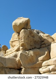 A boulder poised on the edge against a blue sky in the desert of southern California.
