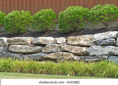 Boulder retaining wall at a commercial site with Inkberry Holly and Daylily