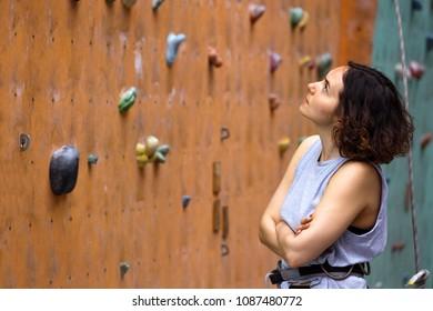 Bouldering, beautiful girl look on the climbing wall