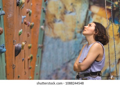 Bouldering, beautiful girl look on the climbing wall. Assessment of their capabilities.