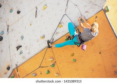 bouldering, girl climbing up the wall