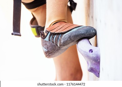 bouldering, girl climbing up the wall. climbing shoes in close-up