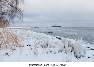 Boulders covered with snow along the Baltic sea shore, Estonia. Winter frost.