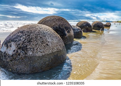 Boulders Moeraki - a group of spherical boulders on the beach Koekokhe. Ocean tide. Travel to New Zealand. The concept of active, eco and photo tourism