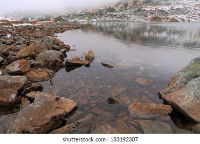 Boulders near glacier lake, morning mist and early snow in the mountains
