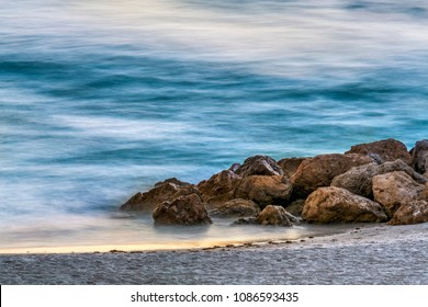 Boulders on a sandy beach are photographed with a long exposure that gives waves an abstract quality at sundown.