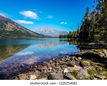 Boulders and rocks in the foreground create an entrance to a magnificent view of Leigh Lake and mountains in the distance, in Grand Teton National Park in Wyoming.Forest lands are also seen at the sho