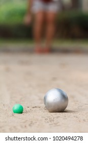 Boules or petanque ball in the match and player in back