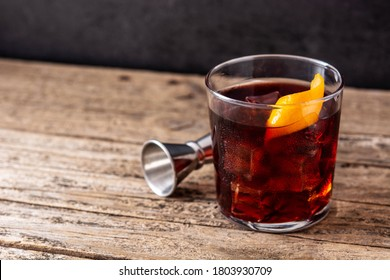 Boulevardier cocktail and orange zest on wooden background.Copy space