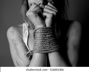 bound hands of woman on gray background.