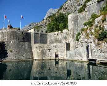 Boundaries of a fortress around the city of Kotor in Montenegro with its reflex on the water. Kotor. Montenegro. August 2016