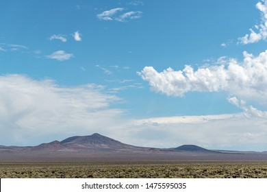 The boundary of the Nellis Air Force Range Nevada Test Site near Area 51 unnamed volcanic buttes  beyond the military  base border fence