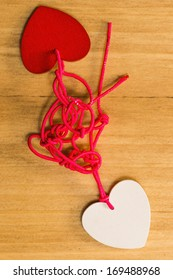 Bounding love: Two hearts bound together with pink thread