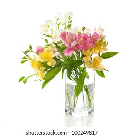 Bouquet of Alstroemeria flowers  in transparent vase isolated on white background.