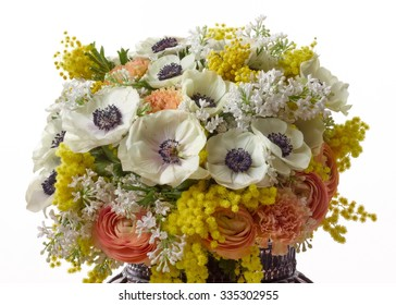 bouquet from anemones, mimosa, lilac, carnations and ranunculus on white background