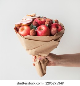 Bouquet of apples and lychee with   gingerbread cookies in shape of heart on a white background. Hand holding a beautiful fruit bouquet.  Gift for lover.