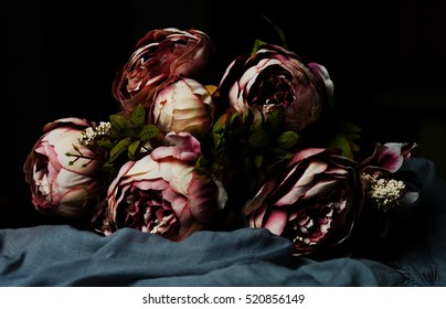 bouquet of artificial dark pink peonies on a gray background