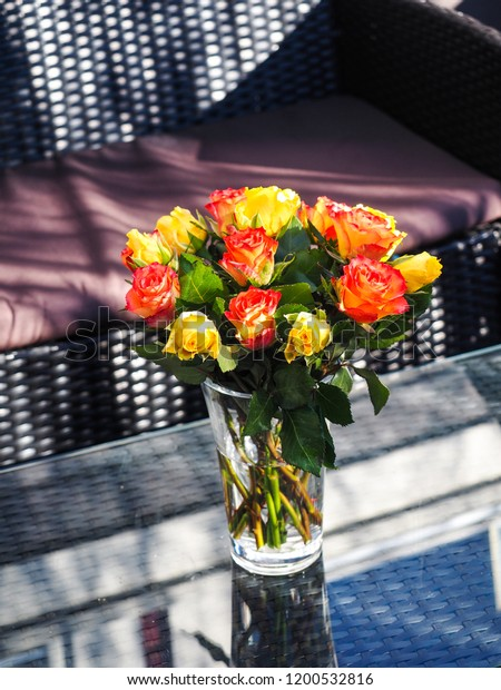 Bouquet of assorted roses in a glass vase, on rotting table with glass top next to patio furniture outdoors at summer