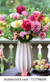 Bouquet of asters and dahlias flowers in a white vase standing on table. Vintage composition still life.