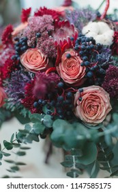 Bouquet of autumn flowers in red, burgundy and shades of Marsala. Ingredients: protea, roses, berries, eucalyptus, cotton flower, lotus flower, chrysanthemum, ornamental cabbage. Flower composition.