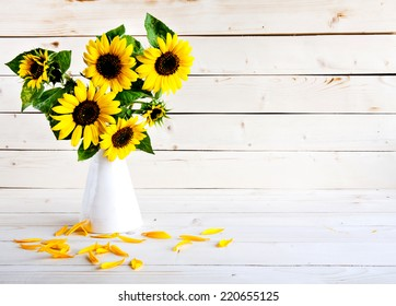 A bouquet of autumn sunflowers in a vase on a grungy wooden table.