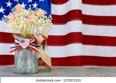A bouquet of babies breath and US flags in a tin pitcher in front of a larger flag in the background. Good for any US holiday.