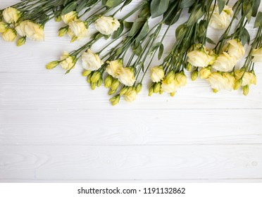 A bouquet of beautiful flawers on a white wood table.Flowers background.A portrait of lithiantys bouquet top view.Flowers flat lay with design space.
