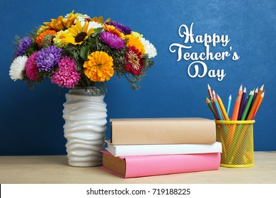 A bouquet of beautiful flowers and a stack of books on a table on a blue background. Concept Teacher's Day.