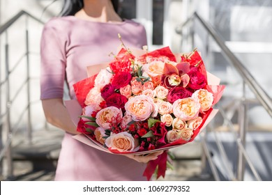 bouquet of beautiful flowers in women's hands. Floristry concept. Spring colors. the work of the florist at a flower shop. Horizontal photo