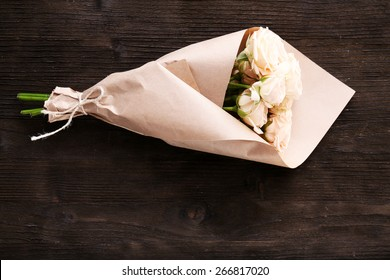 Bouquet of beautiful fresh roses wrapped in paper on wooden background