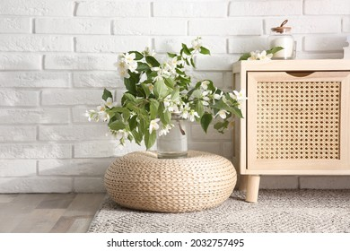 Bouquet of beautiful jasmine flowers in glass vase near white brick wall indoors
