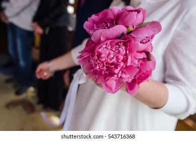 Bouquet of beautiful peonies held by bride