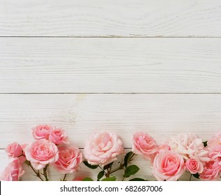 Bouquet of beautiful pink roses on white wooden background.Top view.Copy space