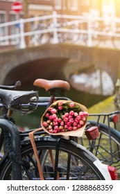 bouquet of beautiful pink tulips lie on the trunk of the bike. Amsterdam