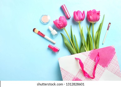 Bouquet of beautiful pink tulips in package and cosmetics on blue background. Concept international women's day, March 8. Top view, copy space,