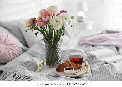 Bouquet of beautiful ranunculuses, croissant and tea on bed indoors