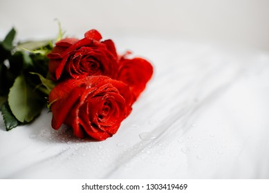Bouquet of Beautiful red roses with water drops macro picture in the morning warm sunlight. Horizontal Close up view with copyspace.  Marble table