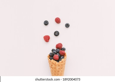 Bouquet of blueberries and raspberries in a waffle cone. Minimal style on a white background. The concept of delicious summer desserts and good nutrition.