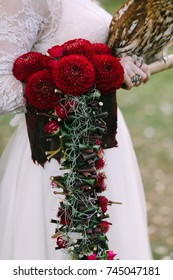 Bouquet with bordeaux dahlias on bride hand. Wedding decoration. Flowers dahlias. Close-up.