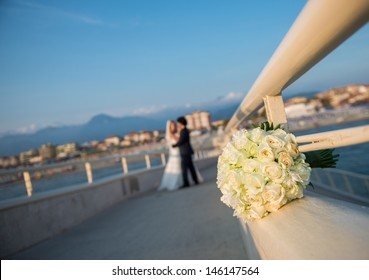 Bouquet, bride and groom. Focus on the bouquet